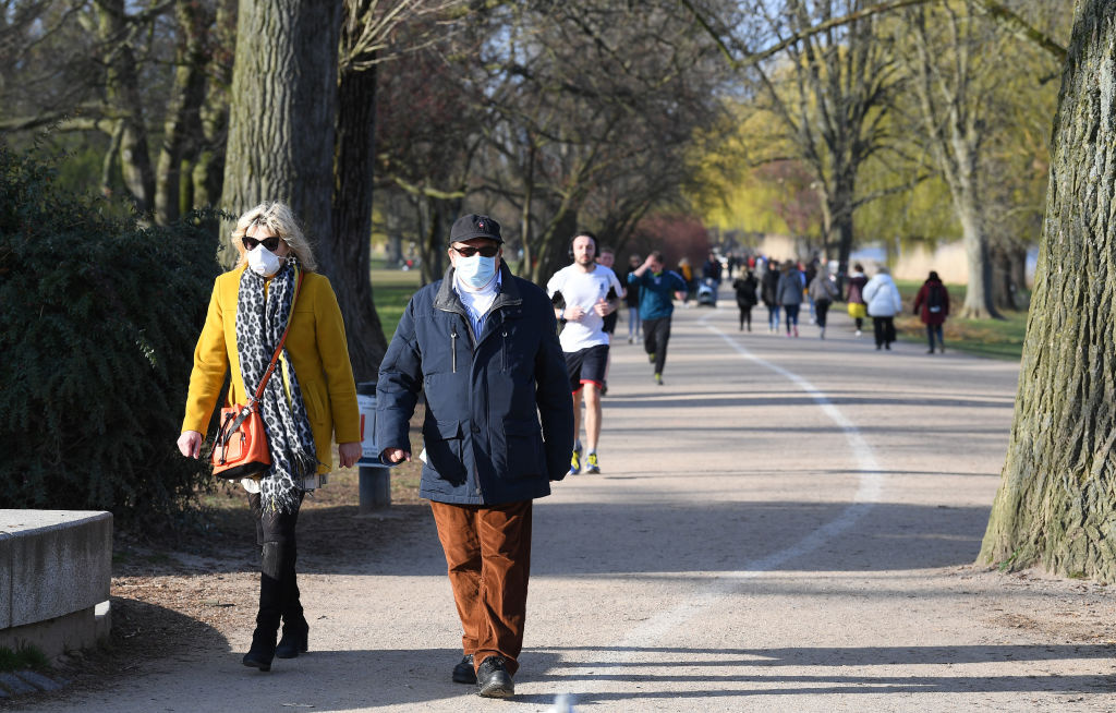 A couple are seen wearing protective masks as the walk by the Aussenalster during the coronavirus crisis on April 4 in Hamburg, Germany.