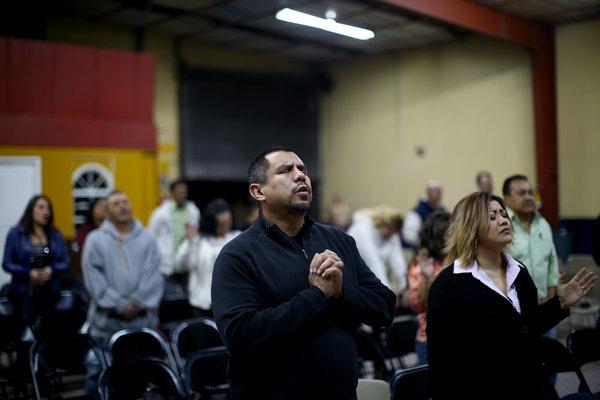 Pastor Robert Salazar (center) prays before giving his sermon at the