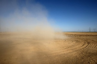 Dust billows as a farmer plows a dry field near Buttonwillow, California. Central Valley farmers and farm workers are suffering through the third year of the worsening California drought with extreme water shortages and job losses.