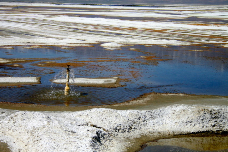 A vast network of sprinklers sends water bubbling up into shallow briny pools that keep the dust down.