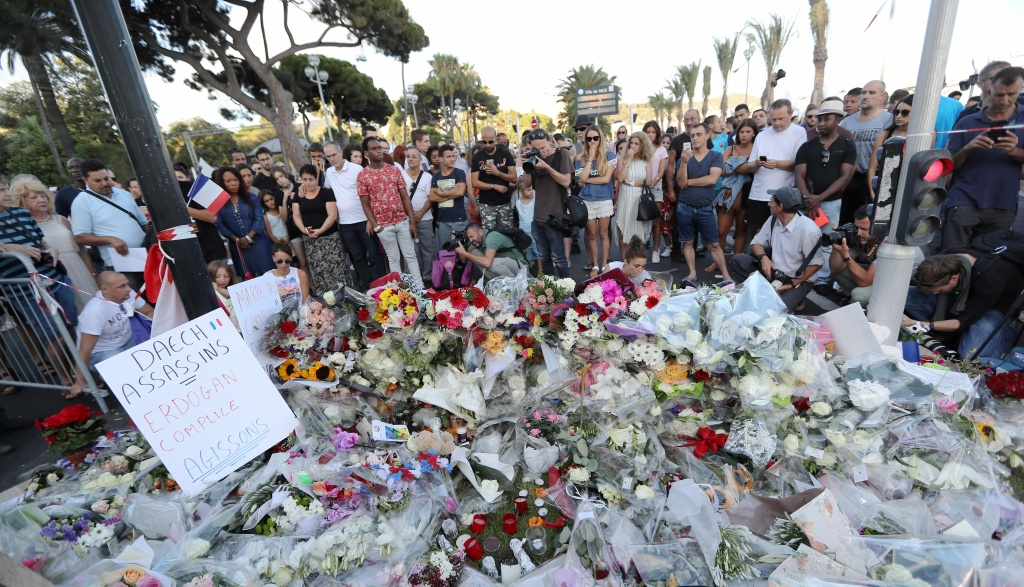 People gather around a makeshift memorial to pay tribute to the victims of an attack in the French Riviera city of Nice on July 15, 2016, a day after when a man rammed a truck through a crowd celebrating Bastille Day, killing at least 84 people.