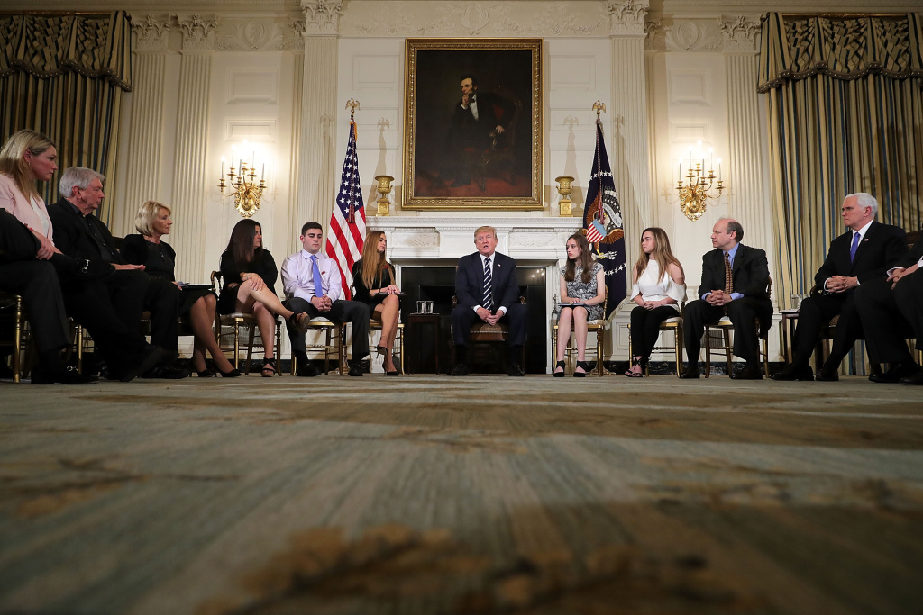 U.S. President Donald Trump (C) holds a listening session with students survivors of mass shootings, their parents and teachers in the State Dining Room at the White House February 21, 2018 in Washington, DC.