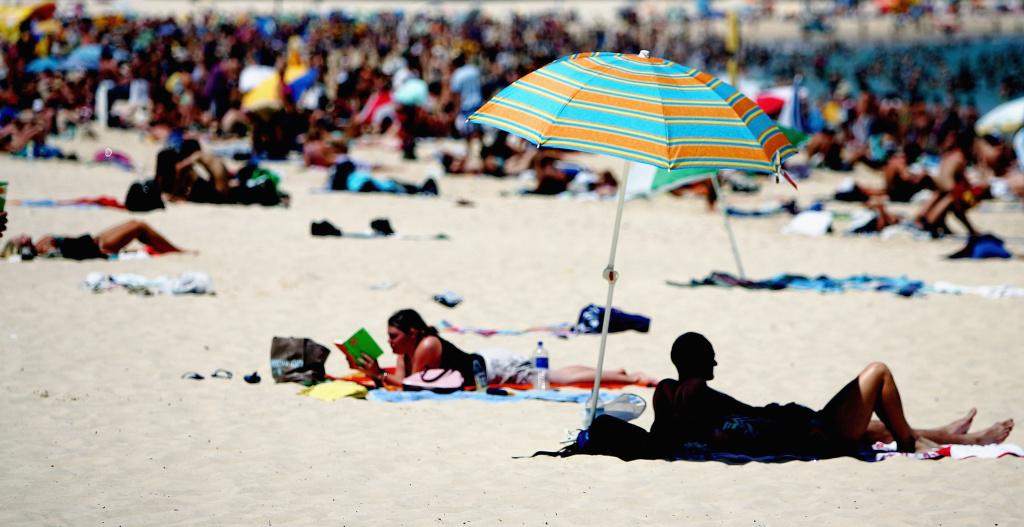 Tourists flock to a crowded beach in Sydney, Australia.