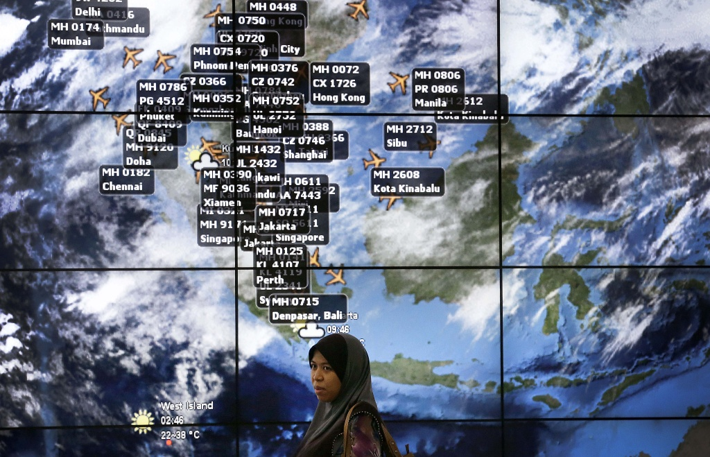 A lady stands in front of an electronic display showing live information of flight positions according to predicted time and flight duration calculations at the Kuala Lumpur International Airport, Sunday, March 16, 2014 in Sepang, Malaysia. Malaysian authorities Sunday were investigating the pilots of the missing jetliner after it was established that whoever flew off with the Boeing 777 had intimate knowledge of the cockpit and knew how to avoid detection when navigating around Asia. (AP Photo/Wong Maye-E)