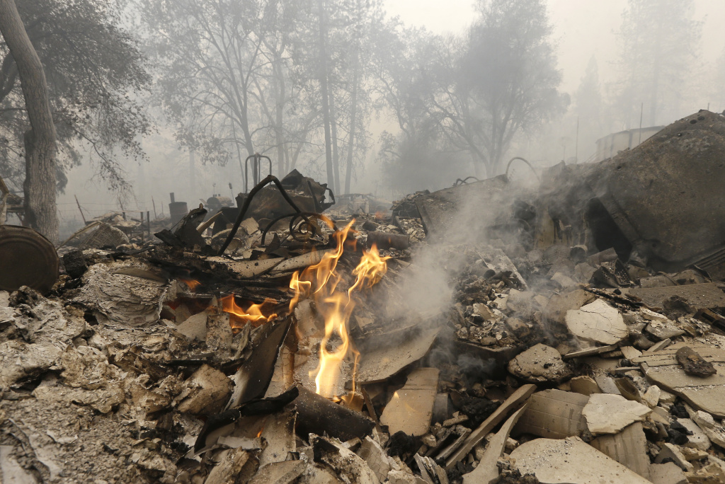 File: Flames burn in the remains of a home destroyed by the Butte Fire, Sept. 12, 2015 in Mountain Ranch, Calif.