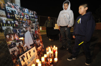 Students Aldo Vazquez, 17, left, and Juan Guerero, 10, right, pause next to a photo of late Augustin Roberto 'Bobby' Salcedo, during candle light vigil at Mountain View High School in El Monte, Calif., Monday, Jan. 4, 2010. Augustin Roberto 'Bobby' Salcedo, an assistant principal at El Monte High School was murdered in Gomez Palacio, Mexico, Dec. 30, 2009. Salcedo and his wife were there for the holidays visiting family members.