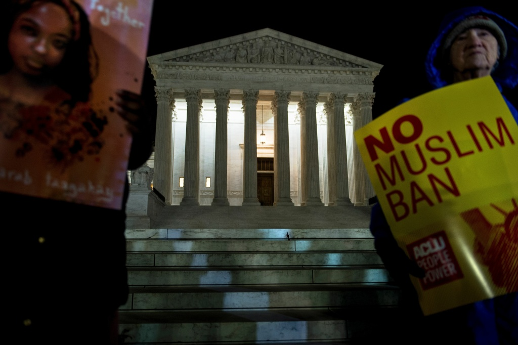 FILE: Activists protest the travel ban outside the U.S. Supreme Court on Dec. 7, 2017 in Washington, D.C.