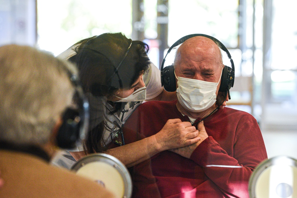 A resident reacts as he talks to his visiting sister at the Domenico Sartor nursing home in Castelfranco Veneto, near Venice, on November 11, 2020 through a glass and plastic device in a so-called