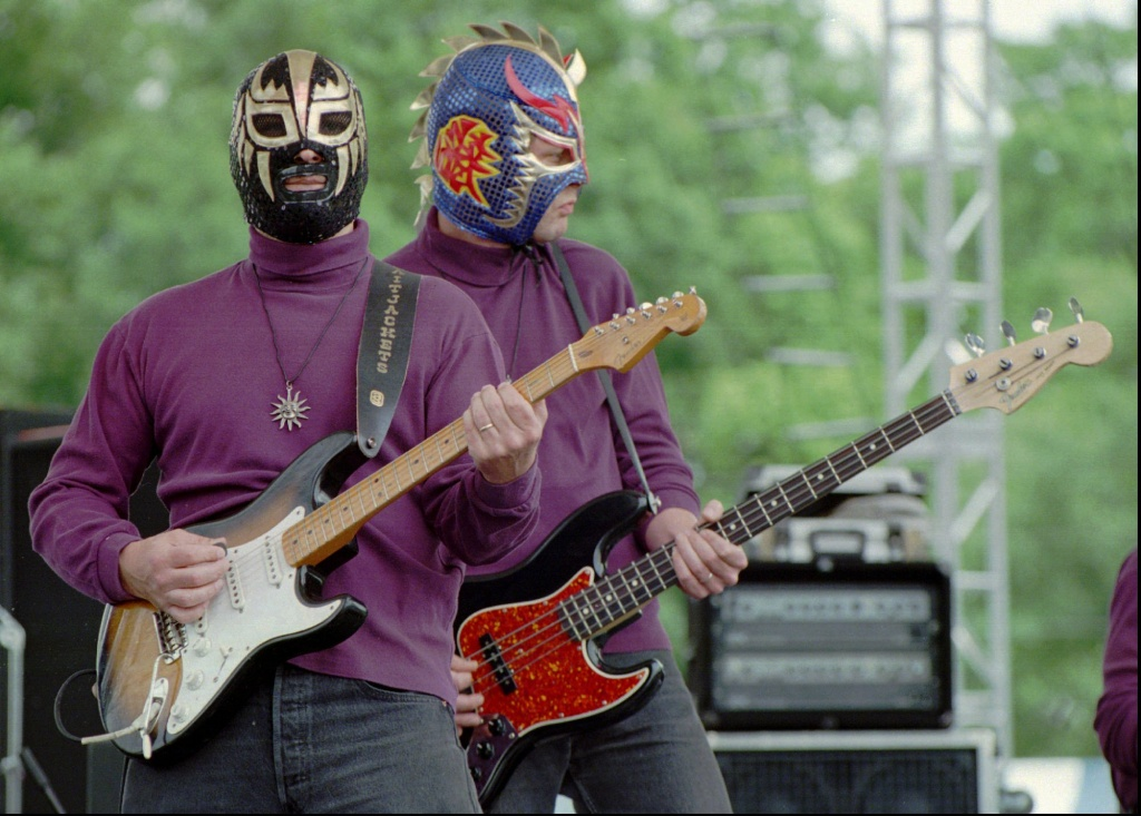Eddy Angel, left, and Scott Esbeck of the Nashville-based band Los Straitjackets, wear Mexican wrestling masks while playing surf music at the Music Midtown festival in Atlanta.