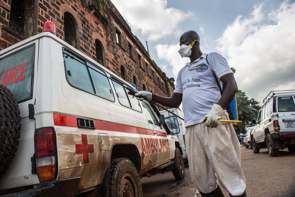 At the main ambulance base in central Freetown, Sierra Leone, a government health worker disinfects ambulances with chlorine spray during the 2014 Ebola outbreak.