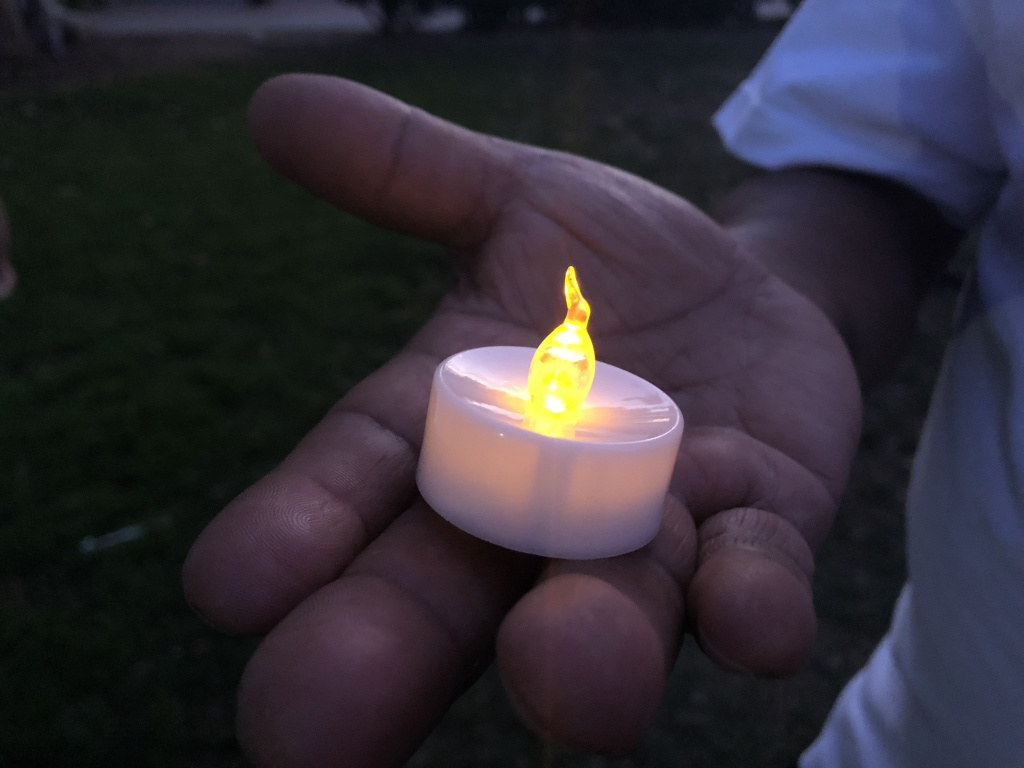 One of the over 100 people gathered at the vigil holds a candle in honor of the victims of the El Paso shooting.