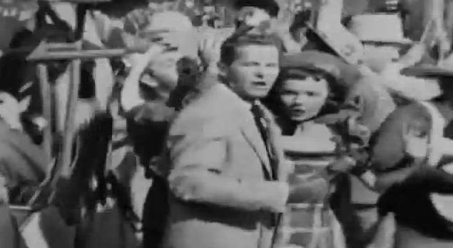 During ABC's live broadcast of the grand opening of Disneyland in 1955, Bob Cummings realizes the camera is on him. Just moments before, he'd been passionately embracing the young woman in a bonnet with the stricken look on her face.