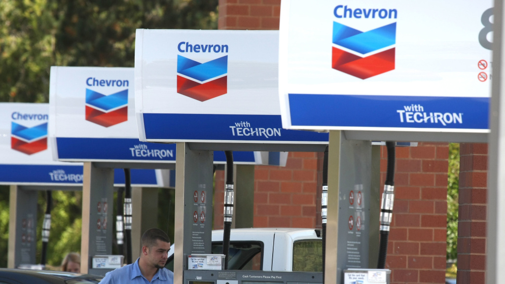 A Chevron customer looks on as he pumps gas into his car in 2009 in Greenbrae, Calif. Chevron is acquiring Anadarko Petroleum for $33 billion in cash and stock.