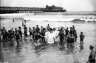 A woman wearing a white baptismal gown is led from the ocean by witnesses in bathing suits after her baptism in the surf next to the Municipal Pier in Long Beach.