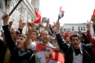 Syrian protesters chant slogans in support of President Bashar al-Assad as they hold up his picture and the national flag during a demonstration in the Old City of Damascus on March 25, 2011.