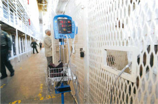 A prisoner patient waits in a cage outside the East Block Death Row clinic, having his vital signs taken through the door port before seeing his attending physician.