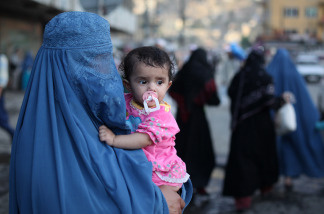 A burqa-clad Afghan woman carries a child through the old town area of Kabul, June 19, 2010. Afghan women worry that peace talks with the Taliban might result in a loss of rights they had slowly regained after the militants' harsh and restrictive rule.