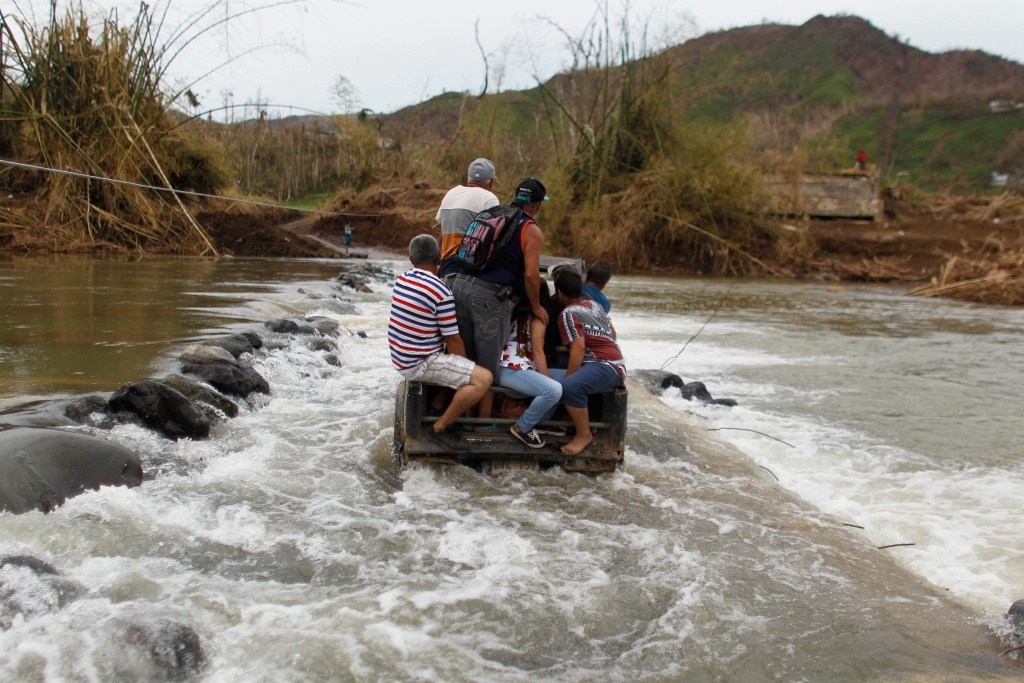 People ride on the back of a 4x4 vehicle into the San Lorenzo River after a bridge was swept away by Hurricane Maria in Morovis, Puerto Rico on September 30, 2017.