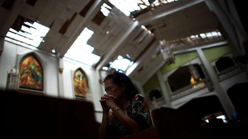 A Filipino woman wipes tears from her eyes while praying at the morning Mass at Santo Nino church, which was damaged by Typhoon Haiyan in Tacloban, Philippines on Sunday. Churches in the area have been serving double duty even after being severely damaged not only for daily masses but serving as refugee centers.