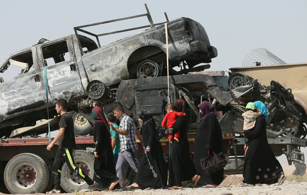 Iraqi displaced people, who have fled violence in Iraq's northern Nineveh province, walk past the wreckage of military vehicles upon their arrival in al-Hamdaniyah, 76 kms west of the Kurdish autonomous region's capital Arbil, on June 18, 2014. Saudi Arabia warned of the risks of a civil war in Iraq with unpredictable consequences for the region, after Sunni militants seized large areas from Shiite-led government forces.