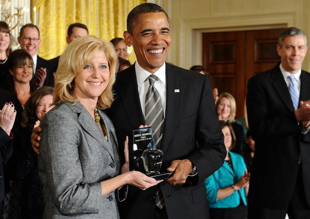 US President Barack Obama (C) gives the 2012 National Teacher of the Year trophy to Rebecca Mieliwocki, a 7th-grade English teacher in California's Luther Burbank High School, during a ceremony in the East Room at the White House in Washington, DC, on April 24, 2012.