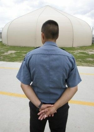 A guard stands outside one of the tent-like structures at the Willacy Detention Center in Texas, May 2007