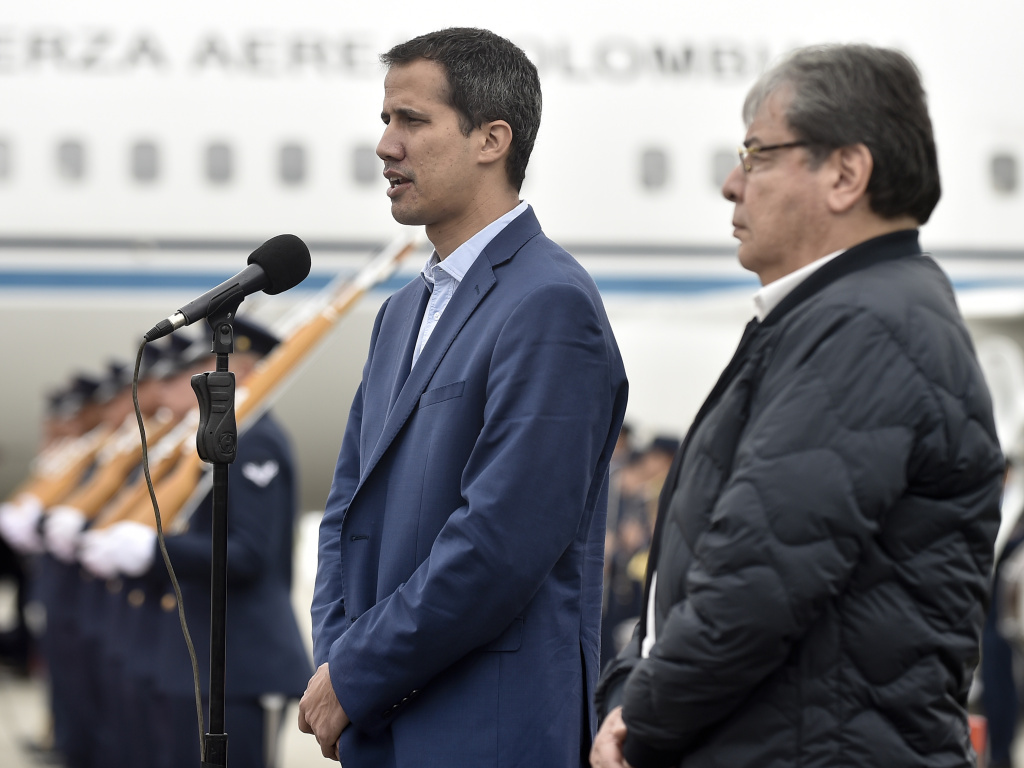 In this photo released by Colombia's presidential press office, Venezuelan opposition leader Juan Guaido makes a statement as Colombian Foreign Minister Carlos Holmes Trujillo stands by at a military airport on Sunday.