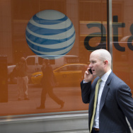 A man using a mobile phone walks past an AT&T store, in June. The New York Times and ProPublica report that the telecom giant helped the NSA spy for decades.