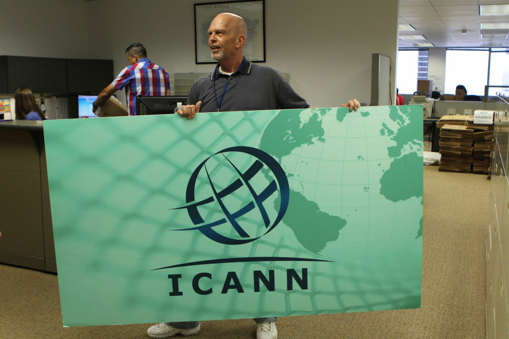 An ICANN employee carries a sign that's been taken down from a meeting room. The agency is moving to a new office in Playa Vista.