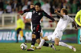 Carlos Vela #11 of Mexico plays the ball as Simon Elliott #7 of New Zealand slides in for the tackle in the second half during their International Friendly match at the Rose Bowl on March 3, 2010 in Pasadena.