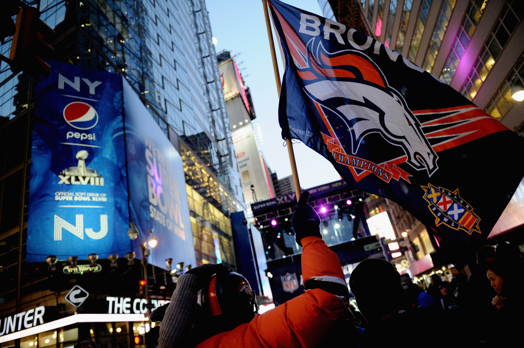 NEW YORK, NY - JANUARY 29:  A Denver Broncos fan waves a flag on Super Bowl Boulevard on January 29, 2014 in New York, New York.  In preparation for the Super Bowl sections of Times Square and Broadway host various games, sponsor booths, and TV broadcasts. (Photo by Maddie Meyer/Getty Images)