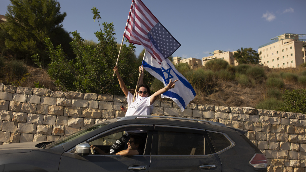 Supporters of President Trump wave U.S. and Israeli flags from a car last week headed for a rally outside the U.S. Embassy in Jerusalem.