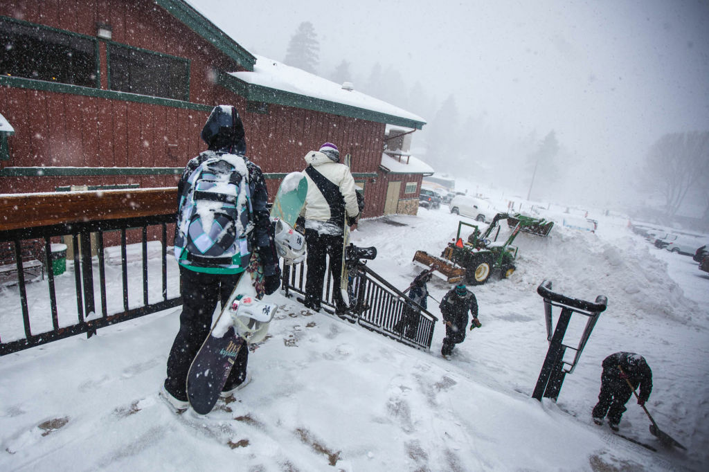 A tractor piled snow as more fell on one of the best days of the year for new powder at Bear Mountain.