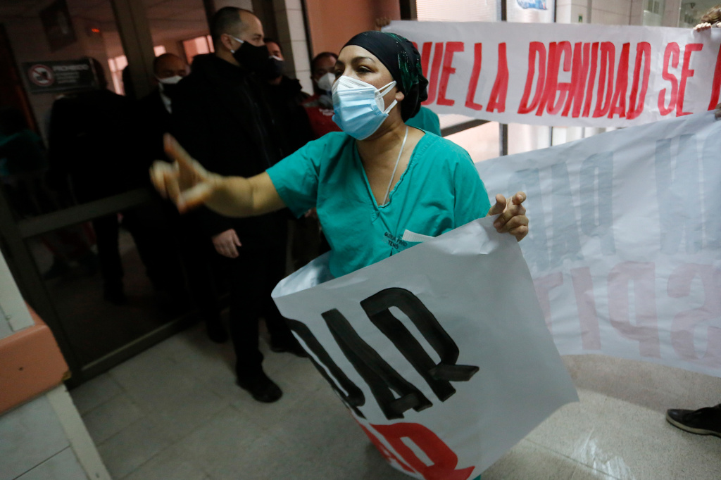 A nurse protests Chile's handling of the coronavirus pandemic. The country now has the highest per capita infection rate of any major country — 13,000 cases for every 1 million people.