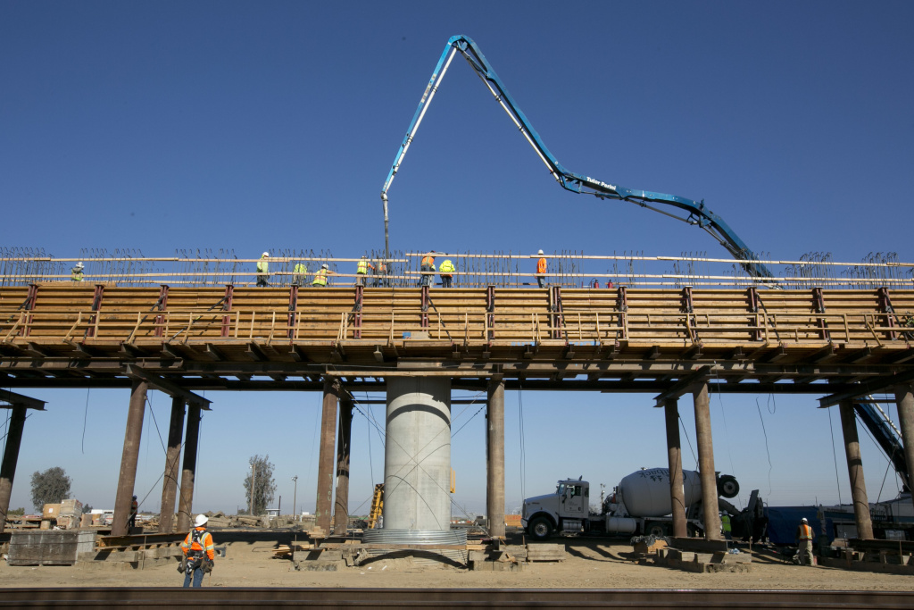 In this photo taken, Wednesday, Dec. 6, 2017, workers pour concrete on to one of the elevated sections of the high-speed rail that will cross over the San Joaquin River, near Fresno.