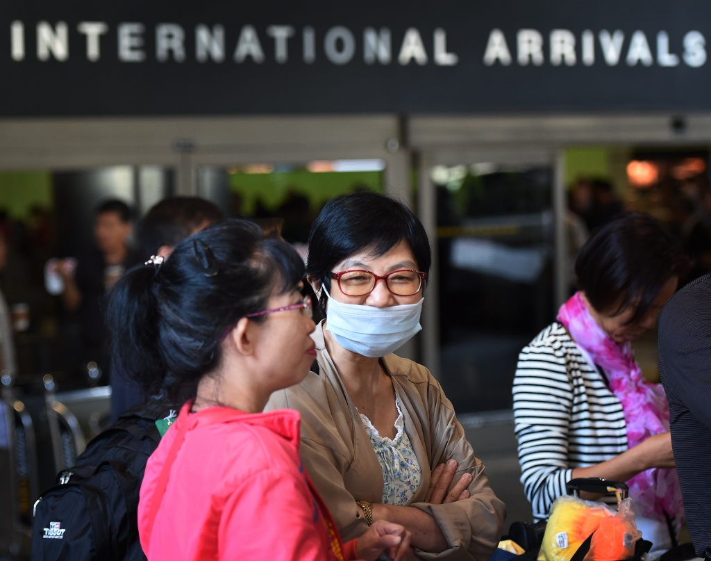 A passenger arrives wearing a face mask at Los Angeles International Airport as fear of the Ebola virus continues to grow in the US on October 17, 2014. On Wednesday, October 29, 2014, California's top health official said the state would being requiring a 21-day quarantine for people traveling from Ebola-stricken nations who had come into contact with patients infected with the virus.