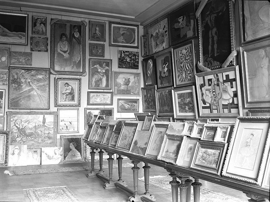 A photo taken by the Nazis during World War II shows a room filled with stolen art at the Jeu de Paume museum in Paris. Using improved technology and the Internet, the French government is making a renewed push to track down the rightful owners of art looted by the Nazis.