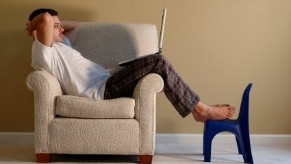 Man sitting on a club chair reading from his laptop.