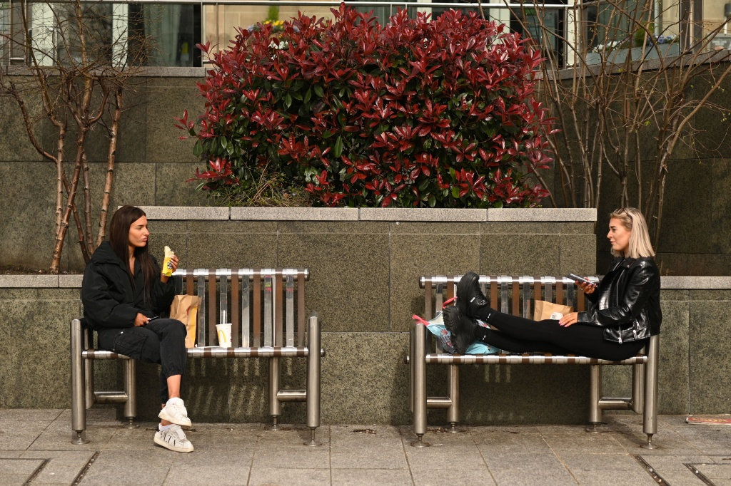 Two friends enjoy their lunch together at a safe distance in central Leeds on March 21, 2020, a day after the British government said it would help cover the wages of people hit by the coronavirus outbreak as it tightened restrictions to curb the spread of the disease.