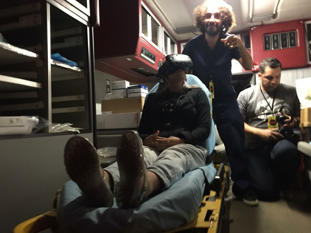 Fawn Quinn looks around the ambulance during the Flatline VR experience. Co-Creator Julian McReas stands above Quinn.