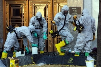 A hazardous material worker sprays his colleagues after they came out from an anthrax search at Dirksen Senate Office Building November 18, 2001 on Capitol Hill in Washington, DC.