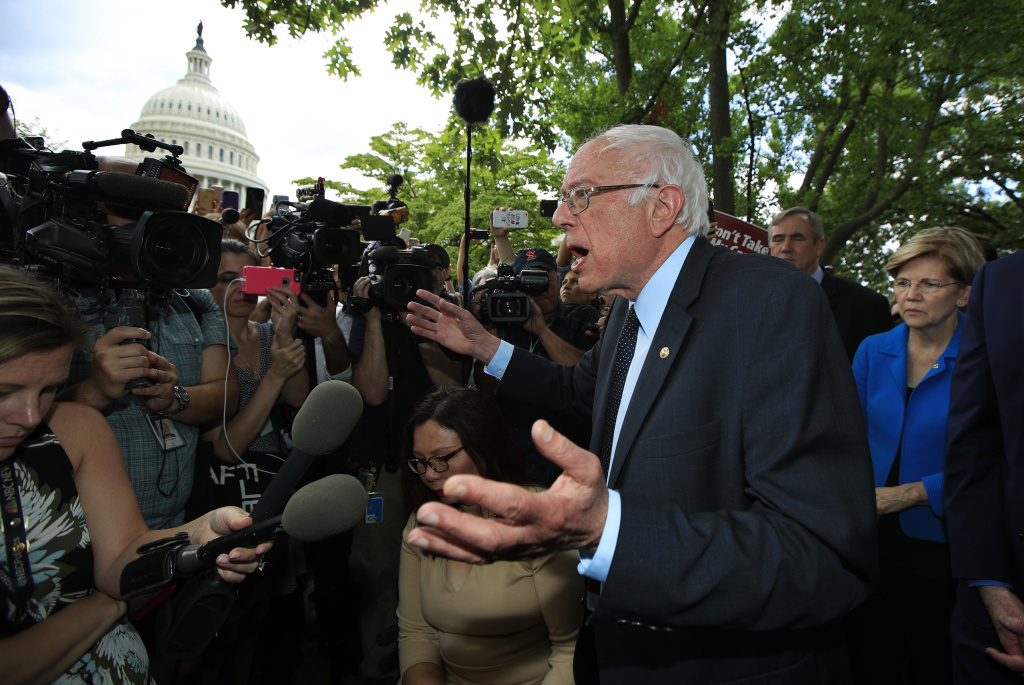 Sen. Bernie Sanders, I-Vt., together with Democratic Senators, including Sen. Elizabeth Warren, D-Mass., right, speaks to supporters outside the Capitol in Washington, Tuesday, July 25, 2017, after the Senate voted to start debating Republican legislation to tear down much of the Obama health care law. (AP Photo/Manuel Balce Ceneta)