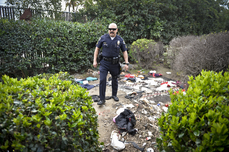 An officer with the Anaheim Community Policing Team checks an apartment where officers heard yelling Thursday afternoon.
