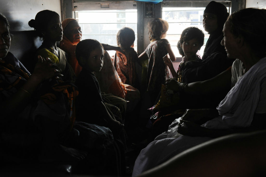 Indian women and children wait inside a darkened train carriage at a railway station in New Delhi on July 31, 2012.