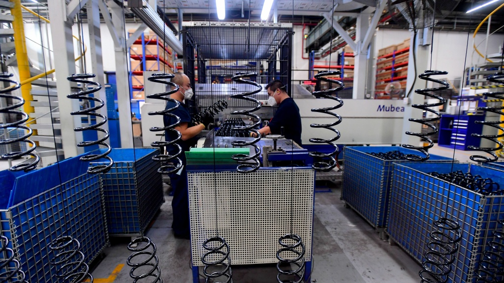 Employees work on automobile parts at a production line at the BMW factory in Shenyang, China on Nov. 22.