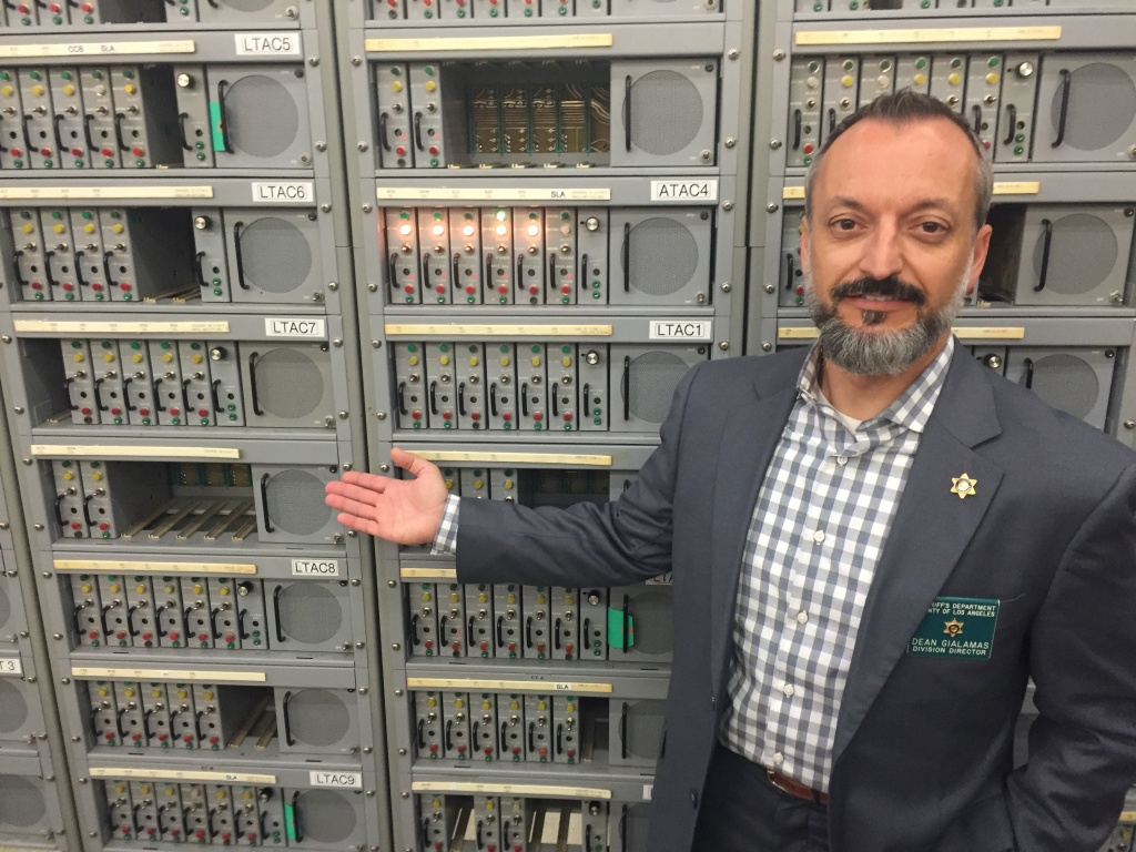 Dean Gialamas, who directs the sheriff's technology and support division, in front of the mechanical switches at the dispatch center.