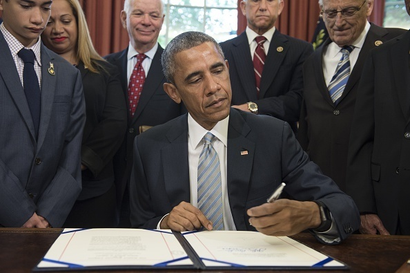 President Barack Obama signs S. 665, the Rafael Ramos and Wenjian Liu National Blue Alert Act of 2015, in the Oval Office on May 19. The act, named after two police officers who were killed in New York, will assist the National Blue Alert system to apprehend violent criminals who have injured or killed police officers or who have made an imminent or credible threat to cause serious injury or death of a law enforcement officer.