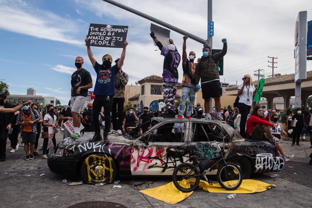 Demonstrators jump on a damaged police vehicle in Los Angeles on May 30, 2020 during a protest against the death of George Floyd, an unarmed black man who died while while being arrested and pinned to the ground by the knee of a Minneapolis police officer.