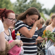 A woman cries at a make shift memorial site on Saturday near the Olympia shopping center where a shooting took place leaving nine people dead the day in Munich, Germany.