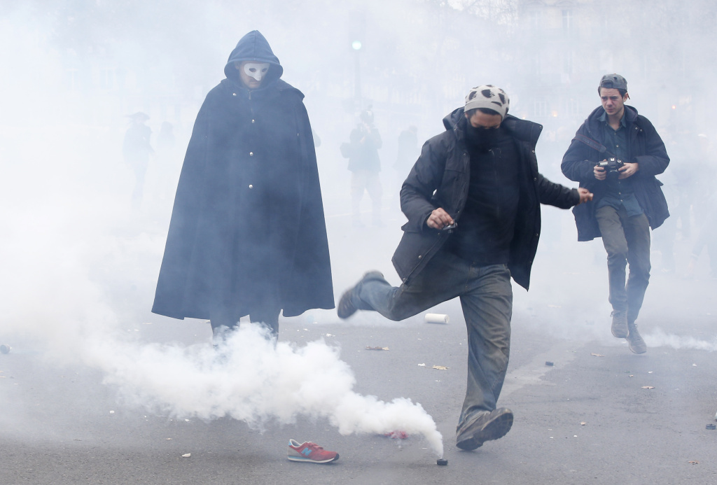 A demonstrator kicks a tear gas canister during clashes with riot police near the Place de la République after the cancellation of a planned climate march.